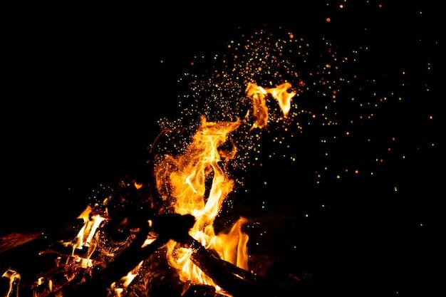 Bosco in fiamme con scintille di fuoco, fiamma e fumo. strane strane strane figure elementali infuocate nella notte nera. carbone e cenere.