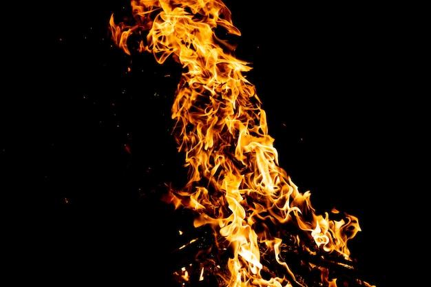 Bosco in fiamme con scintille di fuoco, fiamma e fumo. strane strane strane figure elementali infuocate nella notte nera.