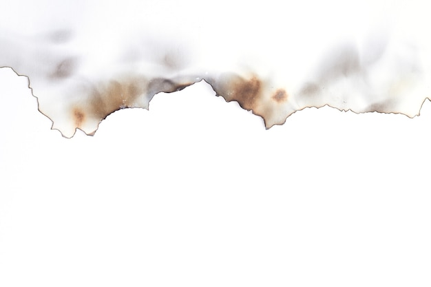 Vecchia carta strappata bruciata isolata su superficie bianca con lo spazio della copia