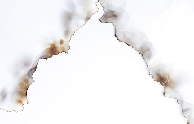 Vecchia carta strappata bruciata su superficie bianca con lo spazio della copia
