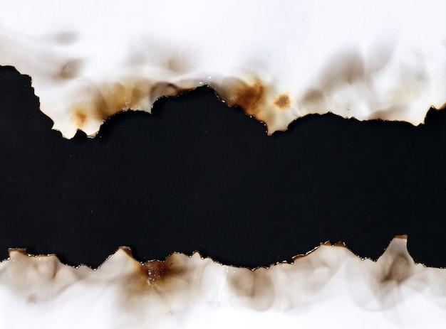 Vecchia carta bianca strappata bruciata sulla superficie nera con lo spazio della copia