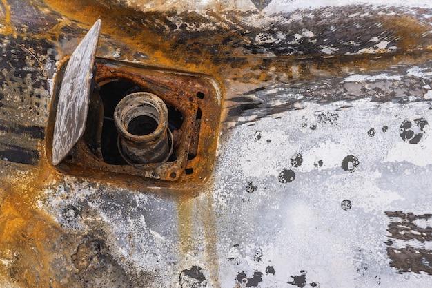 Automobile bruciata, portello di rifornimento del carburante.
