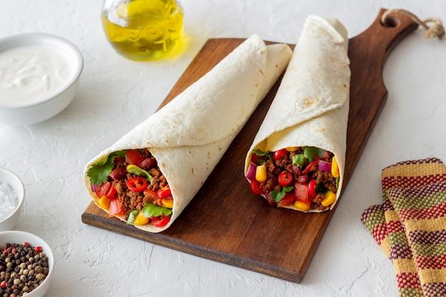Burrito con carne, fagioli, mais, pomodori, cipolle e peperoncino. cibo messicano. ricetta.