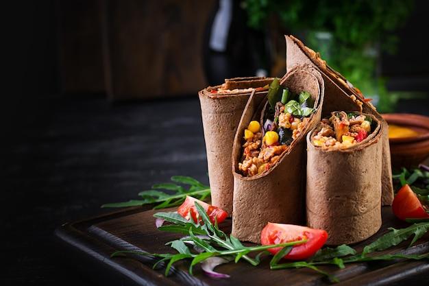 Burritos avvolge con carne di manzo e verdure su fondo di legno scuro. burrito di manzo, cibo messicano.