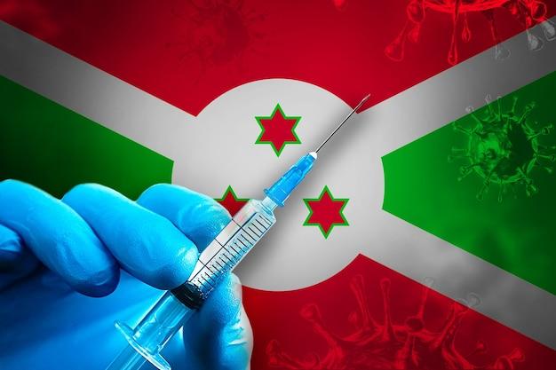 Campagna di vaccinazione del burundi covid19 la mano in un guanto di gomma blu tiene la siringa davanti alla bandiera