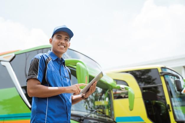 Un membro dell'equipaggio dell'autobus in uniforme e un berretto che sorride mentre utilizza una tavoletta digitale contro la flotta di autobus