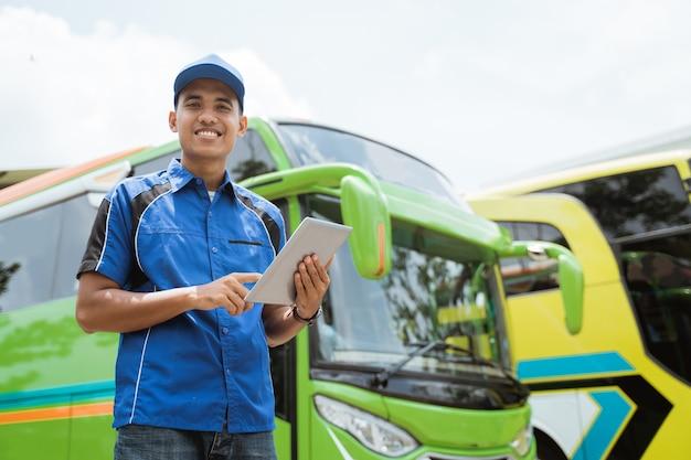 Un membro dell'equipaggio dell'autobus in uniforme e cappello sorride mentre usa una tavoletta digitale contro l'autobus