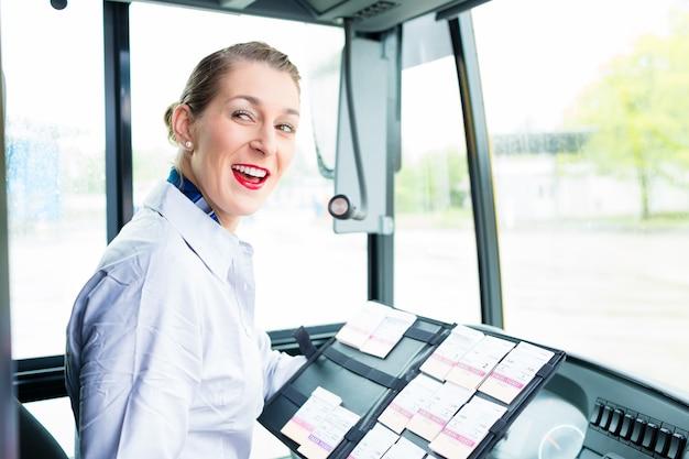 Donna dell'autista di autobus che vende i biglietti dal sedile del conducente