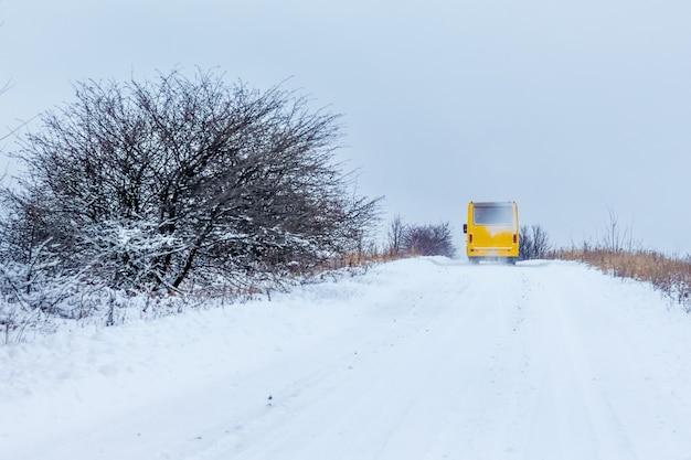 L'autobus si muove lungo la strada innevata in inverno. turismo invernale_