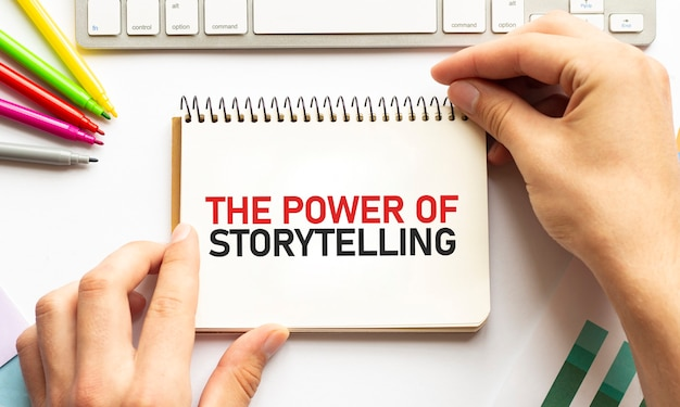 Businesman tenere il blocco note con testo the power of storytelling sfondo bianco affari