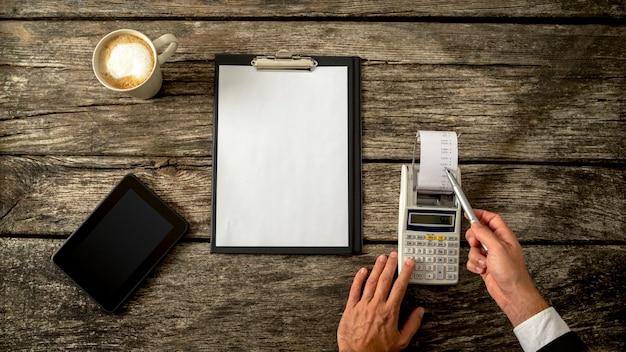 Ragioniere aziendale o consulente finanziario che controlla entrate e uscite per scrivere una relazione annuale mentre fa i calcoli sulla macchina addizionatrice con un foglio bianco davanti a lui