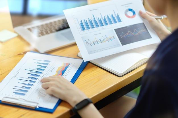 Ragioniere aziendale o funzionario finanziario che cerca e tiene in mano un rapporto di diagrammi grafici grafici finanziari