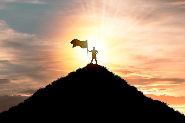 Obiettivo obiettivo di realizzazione aziendale e concetto di successo, silhouette man standing e tenendo la bandiera in cima alla montagna con cielo nuvoloso e luce solare.