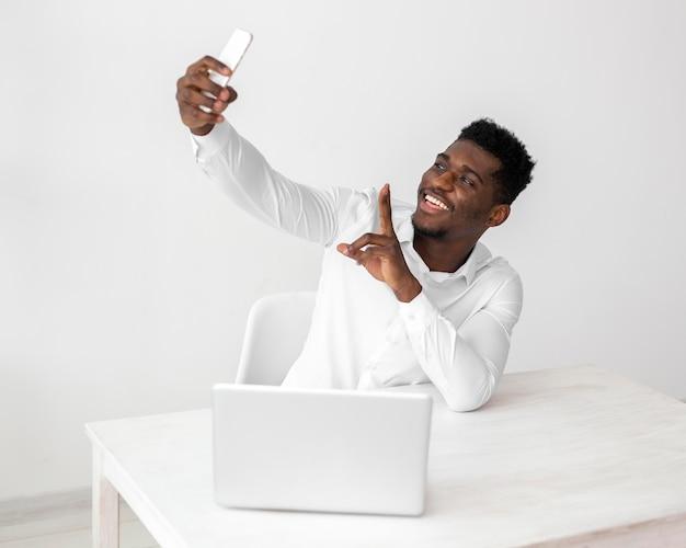 Uomo afroamericano di affari che prende un selfie
