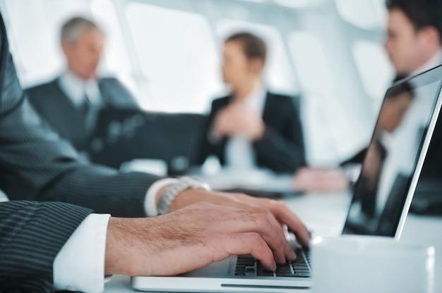 Ambiente d'affari, rapporto di battitura a macchina sul portatile durante la riunione