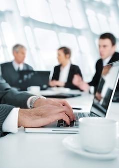 Ambiente aziendale, lavoro su laptop durante l'incontro