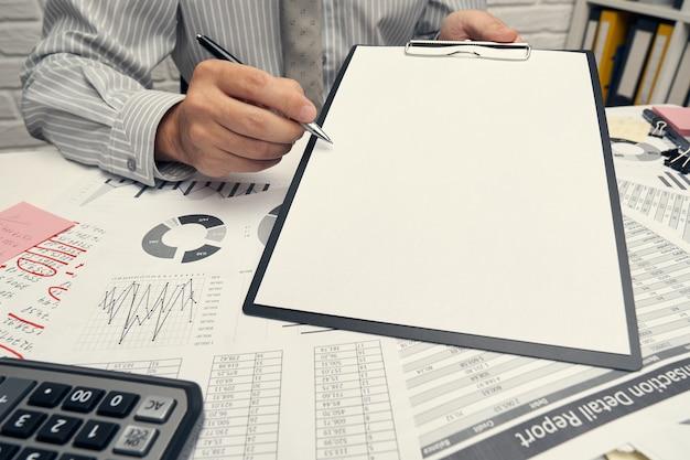 Analisi aziendale e concetto di contabilità - uomo d'affari che lavora con documento, foglio di calcolo, utilizzando la calcolatrice, tablet pc. primo piano della scrivania.