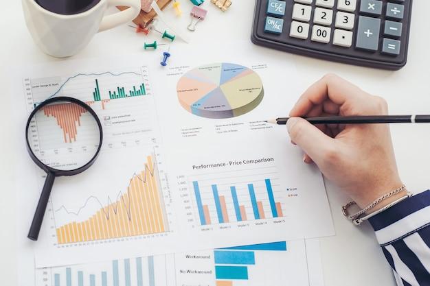 Analista di affari che lavora - mano con penna, calcolatrice, caffè, lente d'ingrandimento, foglio di lavoro e grafico