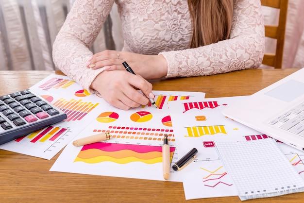 Analista di affari che lavora con i diagrammi con penna e laptop Foto Premium