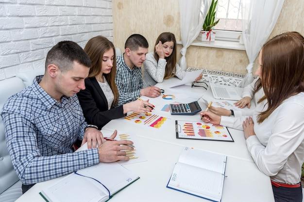 Lavoro di squadra di analisti aziendali in ufficio con grafici e diagrammi