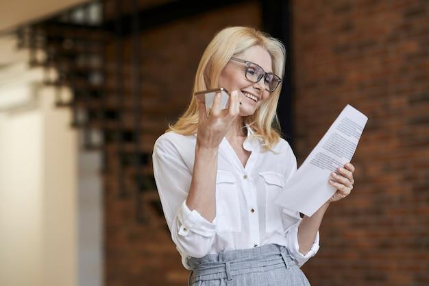 Approccio aziendale elegante donna anziana con gli occhiali e abiti da lavoro sorridenti da leggere e paper