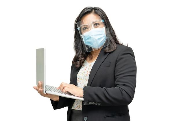 Signora asiatica di affari che porta la protezione per il viso e la maschera per il viso tenendo il laptop.