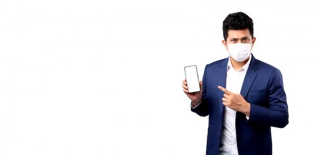 L'uomo asiatico di affari che indossa una maschera è dito indicante malato isolato. con spazio di copia. che tiene il cellulare con schermo vuoto bianco bianco.