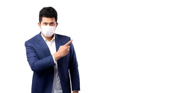 Uomo asiatico di affari che indossa una maschera che indica dito isolato con lo spazio della copia, per prevenire il trattamento sanitario covid-19 di infezione concetto di salute.