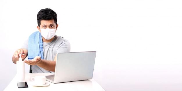 Uomo asiatico di affari che lavora da casa indossando maschera protettiva in quarantena per coronavirus che indossa maschera protettiva. lavorare da casa. lavarsi le mani con alcohol gel. con copia spazio.