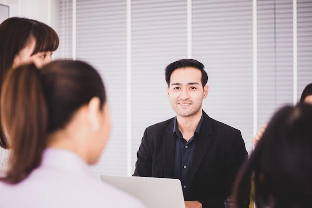 Lavoro di discussione del team asiatico aziendale in ufficio, persone che condividono idee e discutono di progetti, concetto di riunione di brainstorming