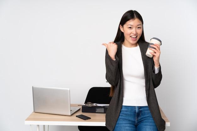 La donna asiatica di affari nel suo luogo di lavoro isolata su spazio bianco con i pollici aumenta il gesto e sorridere