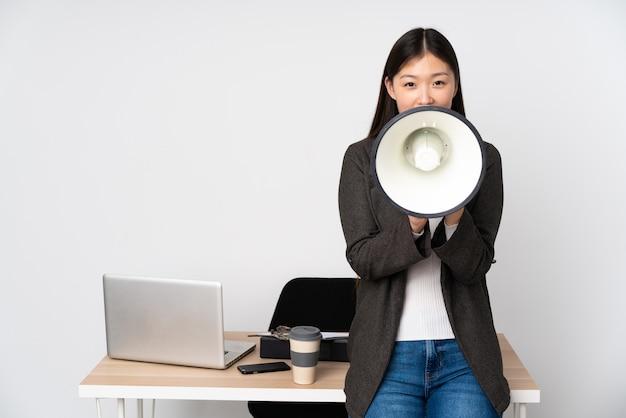 Donna asiatica di affari nel suo posto di lavoro sulla parete bianca che grida tramite un megafono
