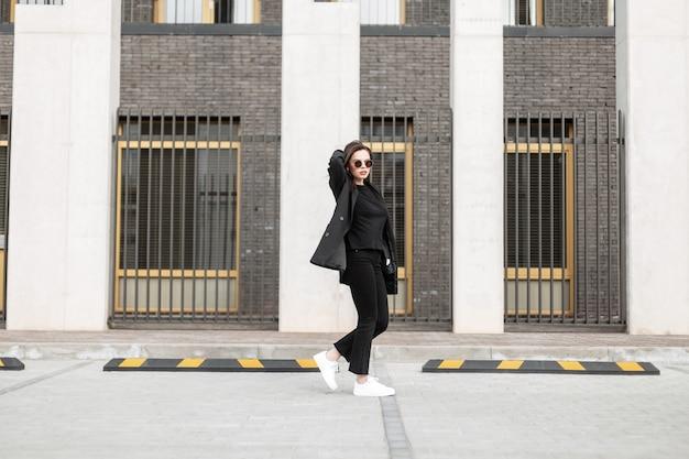 La bella giovane donna d'affari in abiti neri alla moda con un abito formale e scarpe bianche sta camminando vicino a un edificio moderno