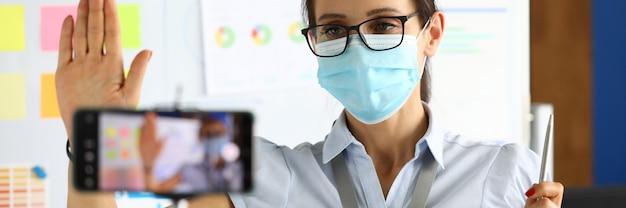 Business blogger in maschera medica protettiva saluta gli interlocutori tramite uno smartphone.