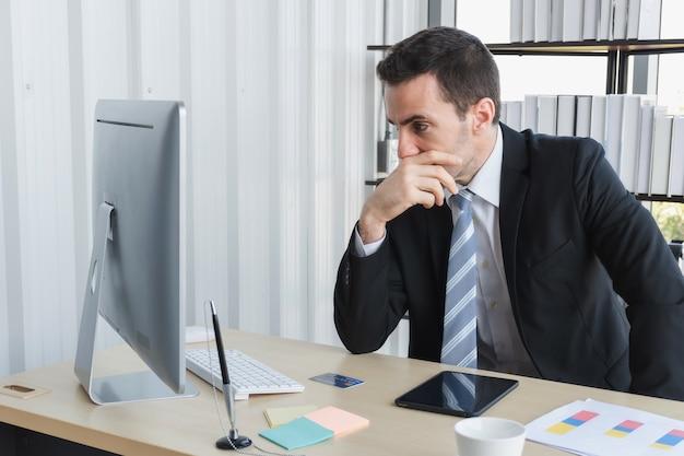 Il capo dell'azienda si sta stressando per i rapporti d'affari mentre chatta al tablet del computer. un uomo d'affari che sottolinea sul lavoro su un tablet pc in ufficio.