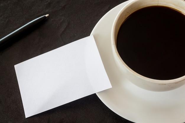 Biglietto da visita e tazza di caffè su sfondo nero