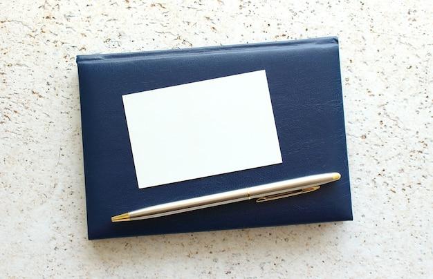 Biglietto da visita sdraiato su un taccuino blu accanto alla penna.