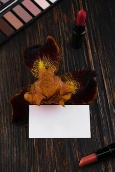 Biglietto da visita rossetti nudi opachi e fiore di iris su un tavolo di legno una tavolozza di ombretti marrone sullo sfondo cosmetici alla moda colori glamour mockup