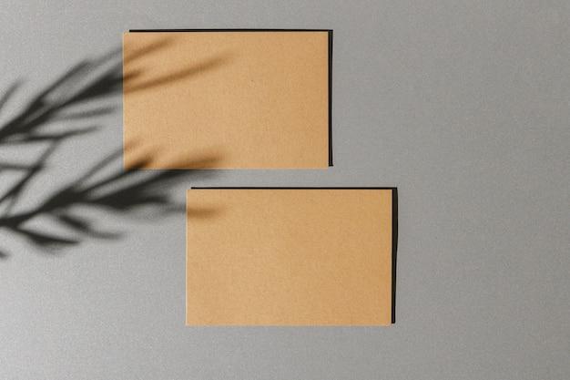 Biglietto da visita su fondo di carta con l'ombra del fogliame