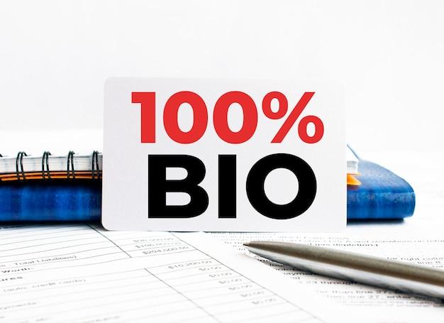 Biglietto da visita con testo 100 per cento bio sdraiato sul taccuino blu