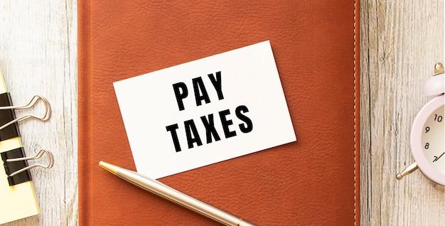Biglietto da visita con il testo pagare le tasse su un tavolo di legno. diario e penna marrone. concetto di affari.