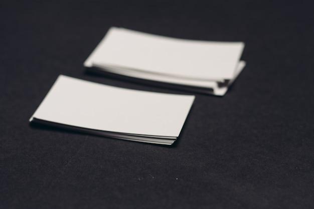 Biglietti da visita su un mockup di tavolo scuro copia spazio