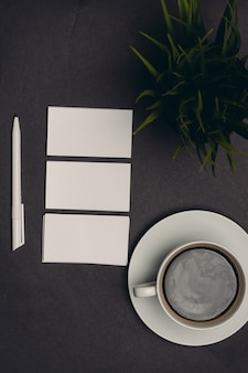 Biglietti da visita sul tavolo e tazza di caffè vista dall'alto della penna