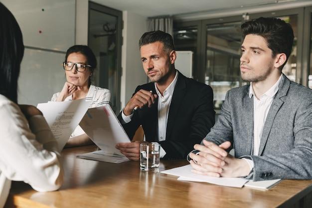 Concetto di affari, carriera e posizionamento - comitato di uomini d'affari seduti al tavolo in ufficio e intervistando la donna durante la riunione