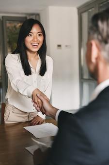 Concetto di affari, carriera e posizionamento - stretta di mano felice della donna asiatica con il capo direttore maschile o il datore di lavoro della grande azienda, dopo negoziati o colloqui di successo