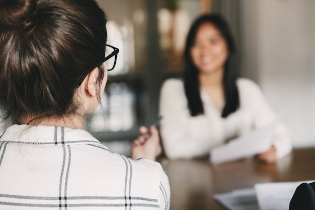 Concetto di affari, carriera e posizionamento: foto dal retro della donna d'affari che intervista e parla con la nuova lavoratrice durante la riunione aziendale