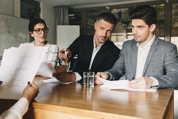 Concetto di affari, carriera e posizionamento: tre direttori esecutivi o capi dirigenti seduti al tavolo in ufficio e intervistando la donna per il lavoro di squadra in azienda