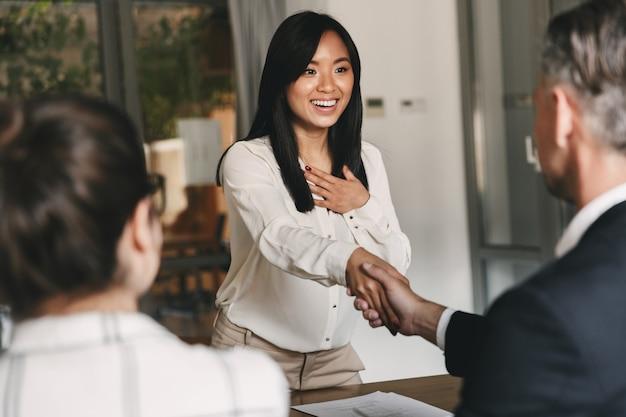 Concetto di affari, carriera e posizionamento - due soci in affari in ufficio che agitano la mano di giovane donna asiatica, dopo negoziati o colloquio di successo