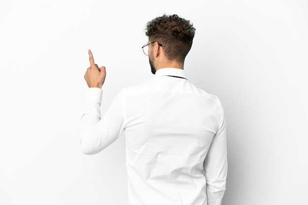 Uomo caucasico di affari isolato su sfondo bianco che punta indietro con il dito indice