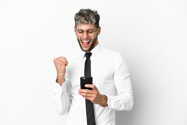 Uomo caucasico di affari isolato su sfondo bianco con il telefono in posizione di vittoria